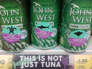 tuna cans on supermarket shelf, with campaign stickers